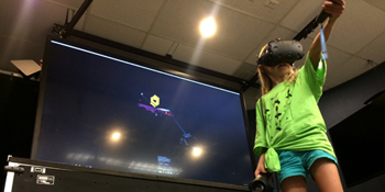 Young girl interacting with a virtual reality display