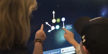 People interacting with a touchscreen at a STScI event