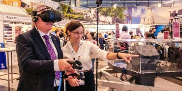 A man in a suit tries a VR headset in a busy conference hall
