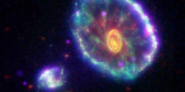This false-color composite image shows the Cartwheel galaxy as seen by NASA Galaxy Evolution Explorer, where the first ripple appears as an ultraviolet-bright blue outer ring.