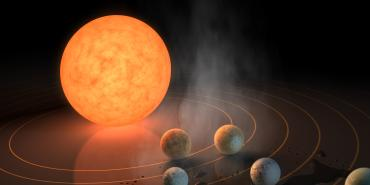Artistic rendering of the TRAPPIST-1 star with seven Earth-size planets orbiting it.