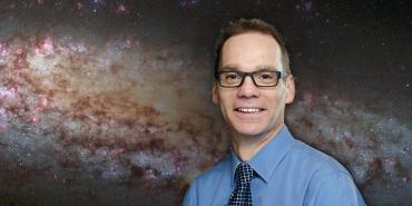 Dr. Kenneth Sembach against a backdrop of Spiral Galaxy NGC 6503