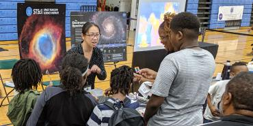 A scientist explains a concept to a family at an event